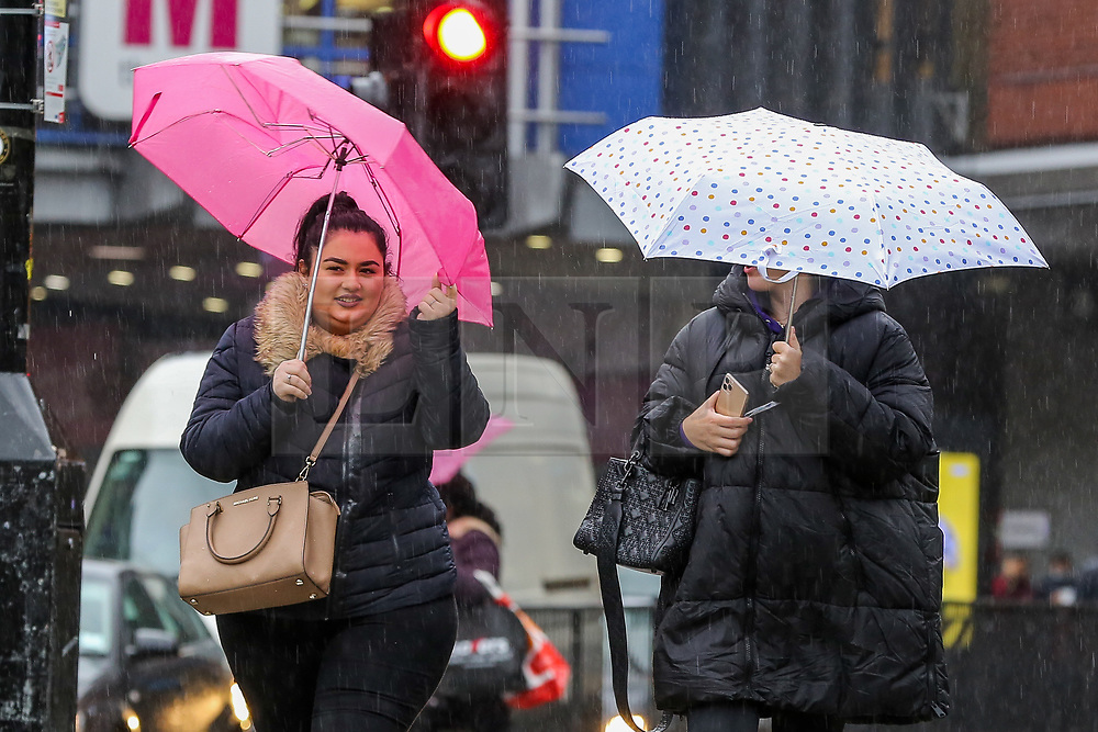 © Licensed to London News Pictures. 02/10/2020. London, UK. Women shelter from rain underneath umbrellas in north London as Storm Alex arrives from Europe. The Met Office forecasts heavy rain and windy weather for the next few days in the capital, caused by Storm Alex. Photo credit: Dinendra Haria/LNP