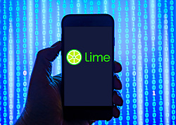 Person holding smart phone with Lime electric bike company logo displayed on the screen. EDITORIAL USE ONLY