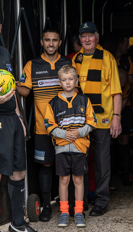 BROMLEY, UK - AUGUST 25: <br /> Barney Williams (Cray Wanderers) with Cray Wanderers mascots before the FA Cup Preliminary Round match between Cray Wanderers and Rusthall at Hayes Lane on August 25, 2018 in Bromley, UK. (Photo: Jon Hilliger / Cray Wanderers)