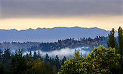 Dark clouds loom over the Cascade Mountain range on in this autumn view from Lake Forest Park. (Mike Siegel / The Seattle Times)