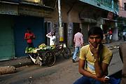 A vegetable vendor drinks at dawn in Sitaram Bazar, Old Delhi, India