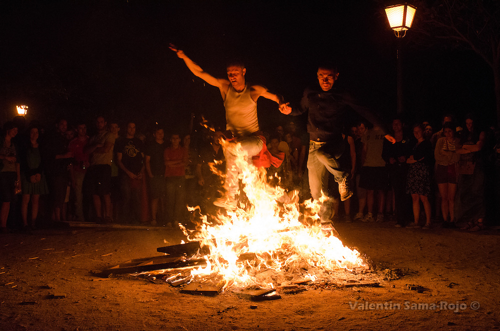 Two men jumping together over a bonfire during Saint John's Eve in Madrid.