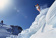 Snowboarder Philippe Bataille does a rail grab while jumping from a snow cornice in the French Alps near Chamonix.