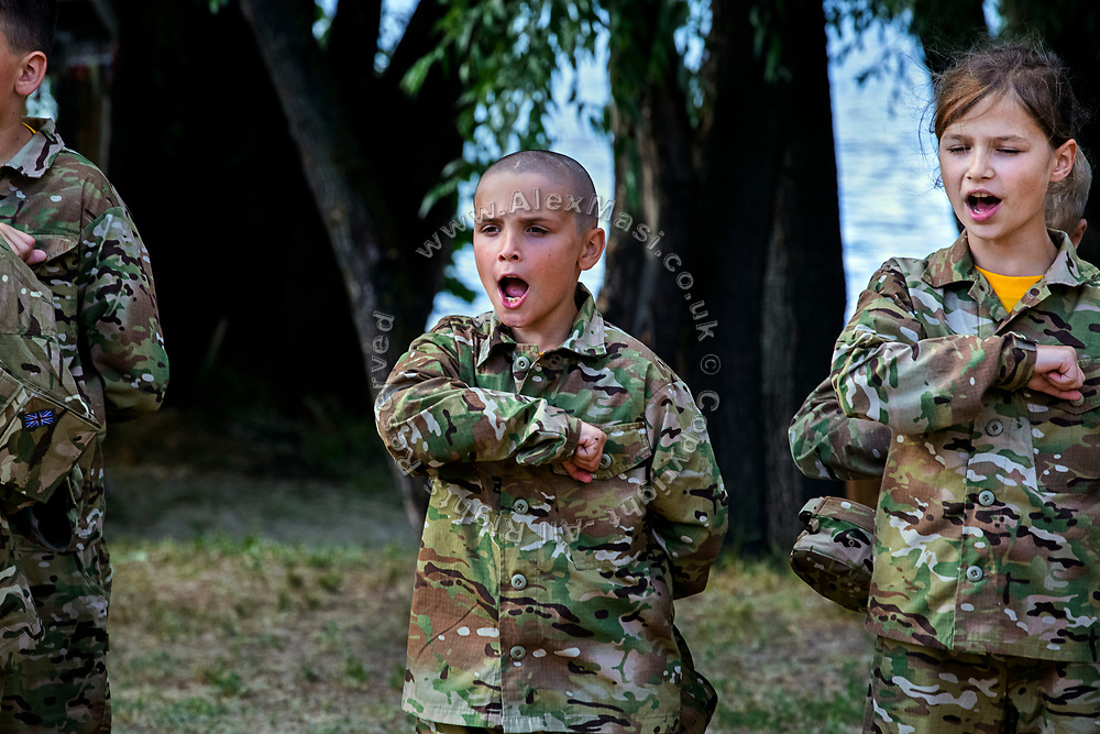 Youngsters participating to the ultra-nationalistic Azovets children's camp are attending a regular ceremony while chanting patriotic slogans with their fists up against their hearts, on the banks of the Dnieper river in Kiev, Ukraine's capital.