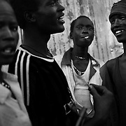 In Yuai market, a group of youth who just came back from the fighting in Pibor country against the Murle tribe after walking for two weeks. They smoke and drink before having to walk more to reach their home with the cattle they stole from the Murle tribe.