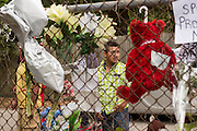A passerby stops to view the makeshift memorial wall at the spot where unarmed motorist Walter Scott was gunned down by police April 12, 2015 in North Charleston, South Carolina. About 100 people showed up for the brief vigil following a healing service at Charity Mission Baptist Church.
