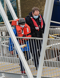© Licensed to London News Pictures. 28/04/2021. Dover, UK. A migrant is helped ashore by a Border Force officer at Dover Harbour in Kent after crossing the English Channel. Photo credit: Stuart Brock/LNP