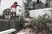 In the cemetery there are no sewerage or piped water. All members of the families residing within the cemetery search for water together. <br /> A girl jumped from grave to grave with bottels in hand, to fill with clean water.
