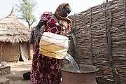 Mariam, 14, pours water she just brought back from a UNICEF-sponsored pump into large ceramic pots at her home in the village of Game, Guera province, Chad on Tuesday October 16, 2012.