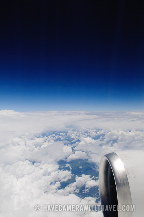 View out a plane window above the clouds, with a clear blue sky above