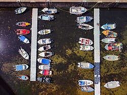 Aerial view from drone of fishing boats in harbour at historic village of Gardenstown on Moray firth Coast in Aberdeenshire, Scotland, Uk
