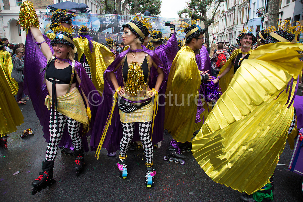 Roller skate troupe on Sunday 28th August 2016 at the 50th Notting Hill Carnival in West London. A celebration of West Indian / Caribbean culture and Europes largest street party, festival and parade. Revellers come in their hundreds of thousands to have fun, dance, drink and let go in the brilliant atmosphere. It is led by members of the West Indian / Caribbean community, particularly the Trinidadian and Tobagonian British population, many of whom have lived in the area since the 1950s. The carnival has attracted up to 2 million people in the past and centres around a parade of floats, dancers and sound systems.
