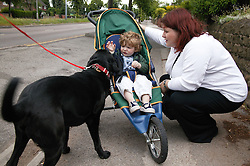 Mother with her baby son in his buggy and fussing a pet dog,