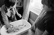 """A two and half year-old girl watches her mother bath her baby brother in the bathroom of her South London home. She looks down at the correct technique that her mum uses by supporting his head with a hand, ensuring the child does not slip further into the warm bath water, the way that many babies drown in even shallow water. Such maternal instincts is how even young children learn to mother and care for their own children in later life, From a personal documentary project entitled """"Next of Kin"""" about the photographer's two children's early years spent in parallel universes. Model released."""