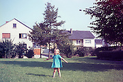A young blonde girl of approximately 3 years-old stands on a lawn looking delighted. She giggles with great mirth at something that pleases her - possibly the way her father has posed her as if she's a ballerina, or maybe because it is her birthday and her present is the blue dress she is showing off to the viewer. The girl holds out her arms while holding a special pair of sunglasses. It is the summer of 1967 and this is a housing estate for British soldiers stationed in Bielefeld, Germany still during the Cold War. The girl's father is a solder serving in the British Army and the they all live in a house nearby with other expat families. Kodachrome film has a wonderful magenta colour cast in mid-tones and where a small light-leak has affected the far right, reminiscent of the classic days of early photography when shifts in color gave a faded look.