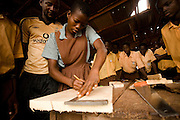 A girl measures a piece of wood during a carpentry class at the Zogbeli Junior Secondary School in Tamale, Ghana on Thursday June 7, 2007. The class is mandatory for both boys and girls.