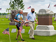 25 MAY 2020 - ROLAND, IOWA: LARRY RITLAND and GLENN KAPPELMANN walk through Roland Cemetery, in Roland, Iowa, a farming community an hour north of Des Moines. Ritland, a Vietnam era veteran, rode his bicycle about 74 miles through central Iowa to honor veterans buried in cemeteries in rural Iowa. In 2020, most public Memorial Day events in Iowa were canceled because of the COVID-19 pandemic, but some families had their own private events. Memorial Day is a federal holiday to honori and mourn the military personnel who have died while serving in the United States Armed Forces. Memorial Day is observed on the last Monday in May.       PHOTO BY JACK KURTZ