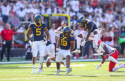 Sep 4, 2021; College Park, Maryland, USA; West Virginia Mountaineers safety Scottie Young (19) celebrates with teammates West Virginia Mountaineers linebacker Lance Dixon (5) and West Virginia Mountaineers safety Alonzo Addae (4) after a stop on defense during the second quarter against the Maryland Terrapins at Capital One Field at Maryland Stadium. Mandatory Credit: Ben Queen-USA TODAY Sports