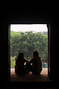 A young romantic couple sit in a window of the ruins of a Madrassa in Hauz Khas built by the 14th century Sultan Firoz Shah Tughlaq