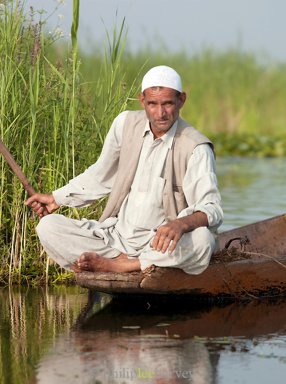 A local man in a boat on Lake Dal, Kashmir, India