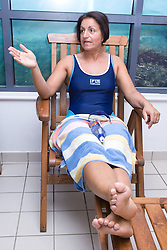 Woman relaxing by the pool side at her sports leisure centre,