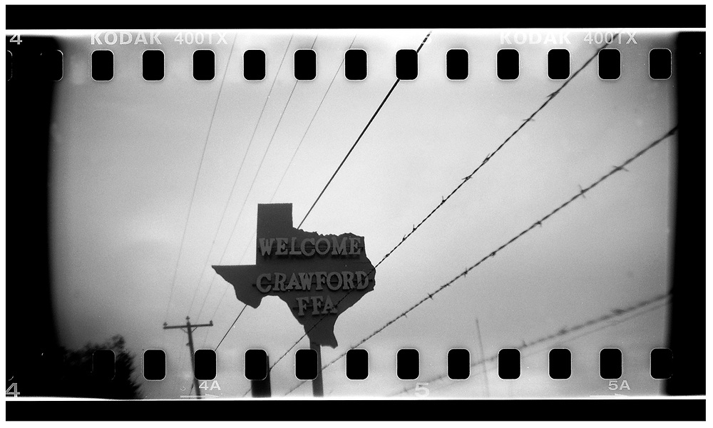 A welcome sign is seen on the road leading to Crawford, Texas, November 10, 2008. U.S. President George W. Bush moved to the small Texas town, population 705, in 1999 during his run for the presidency in 2000. The effect of the image was achieved by shooting 35mm black and white film in a medium format camera thereby exposing the entire negative including the sprocket holes of the film. REUTERS/Jim Young