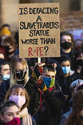 """© Licensed to London News Pictures. 20/03/2021. Manchester, UK. A person in the crowd holds up a placard reading """" Is defacing a slave trader's statue worse than rape? """" Thousands attend a """" Kill the Bill """" and Reclaim the Streets protest demonstration in St Peter's Square in Manchester City Centre in opposition to the Police, Crime, Sentencing and Courts Bill 2021 that is currently before Parliament and after the death of Sarah Everard in London . Photo credit: Joel Goodman/LNP"""