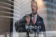 A male model in the window of a menswear outfiters holds a hold-all bag with the word Monday written beneath, plus City workers walking during a quiet lunchtime during the Coronavirus pandemic in the City of London, the capital's financial district, on 29th July 2020, in London, England.