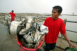 Men who have probably lost everything, including possibly their families find value in scavenging a few items of twisted aluminium to recycle for cash.  This desolate wasteland that was once a bustling portside area at Ulee Lheue close to Banda Aceh.
