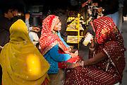 Indian women in saris drinking tea (India)