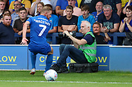 AFC Wimbledon midfielder Scott Wagstaff (7) almost running into a cameraman during the EFL Sky Bet League 1 match between AFC Wimbledon and Accrington Stanley at the Cherry Red Records Stadium, Kingston, England on 17 August 2019.