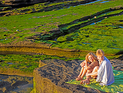 Young friends picnicking on rocky beach at Playa de Azkorri, Getxo, Basque Country, Spain