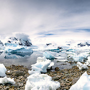 A high resolution panorama of a kayak pulled up on the rocky shore at Cuverville Island on the Antarctic Peninsula.