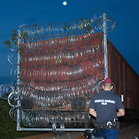 Police officer watches as a train mounted section is taken to the border on the railway to close down the last few meters of the fence on the border between Serbia and Hungary near Roszke (about 174 km South of capital city Budapest), Hungary on September 14, 2015. ATTILA VOLGYI