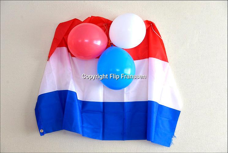 Nederland, Nijmegen, 27-4-2017Op Koningsdag hangen in een zaaltje waar een vrijmarkt gehouden wordt de nederlandse vlag en drie ballonnen in de kleuren rood, wit en blauw.Foto: Flip Franssen