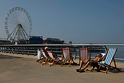 People lounge sunbathing in striped deck chairs, which were banned during the height of the Covid-19 pandemic, with Blackpools Big Wheel in the background as temperatures in the country are expected to soar this week on 7th September, 2021 in Blackpool, United Kingdom. Temperatures in the UK are predicted to soar to highs of 29 degrees celsius, coinciding with a rise in daycation and staycation domestic tourism in the country as a result of Covid-19 precautions that make foreign travel increasingly costly and difficult.