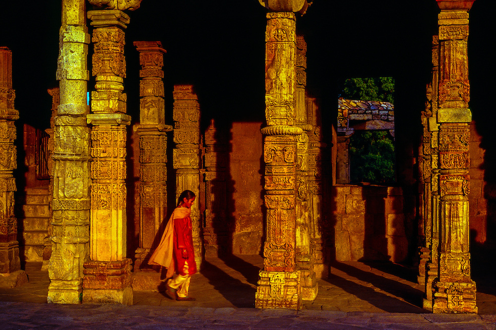 Indian woman walking through an archway leading to the Qutab Minar (fluted tower), New Delhi, India