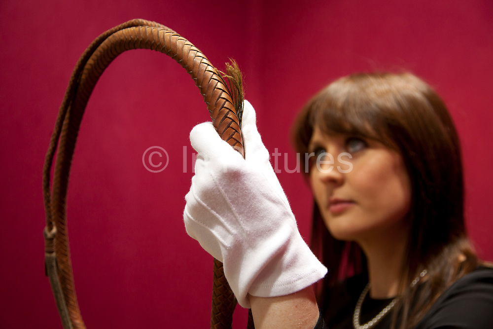 London, UK. Friday 23rd November 2012. Christies auction house showcasing memorabilia from every decade of the past century of popular culture from the industries of film and music. Christie's Specialist Caitlin Graham shows the hand-made bull-whip of kangaroo hide, created by whipmaker David Morgan used in Raiders Of The Lost Ark, 1981, Indiana Jones And The Temple Of Doom, 1984 and Indiana Jones And The Last Crusade, 1989.
