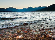 """The peaks of the Livingston Range rise above Lake McDonald at sunrise in Glacier National Park, Montana, USA. Waves caress red shoreline rocks. Since 1932, Canada and USA have shared Waterton-Glacier International Peace Park, which UNESCO declared a World Heritage Site (1995) containing two Biosphere Reserves (1976). Rocks in the park are primarily sedimentary layers deposited in shallow seas over 1.6 billion to 800 million years ago. During the tectonic formation of the Rocky Mountains 170 million years ago, the Lewis Overthrust displaced these old rocks over newer Cretaceous age rocks. Glaciers carved spectacular U-shaped valleys and pyramidal peaks as recently as the Last Glacial Maximum (the last """"Ice Age"""" 25,000 to 13,000 years ago). Of the 150 glaciers existing in the mid 1800s, only 25 active glaciers remain in the park as of 2010, and all may disappear by 2020, say climate scientists."""