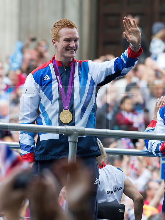 © London News Pictures. 10/09/2012. London, UK . Long Jumper Greg Rutherford waving from a float. Athletes take part in an open top bus victory parade through central London on September 10, 2012 to honour achievements of Team GB in both the Olympic and Paralympic Games. Photo credit: Ben Cawthra/LNP