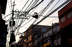 © Licenced to London News Pictures. 26//11/2014. Delhi. India.  <br /> A monkey is seen silhouetted walking across illegal electricity cables in the Chawri Bazar market area of Old Delhi, India, November 26th 2014. <br /> Photo Credit: Susannah Ireland