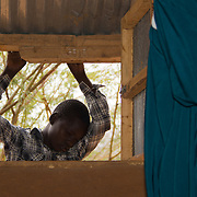 A child joins in with prayers at Dadaab's Gambela church. These refugees from Ethiopia are now part of the Christian minority among Dadaab's largely Muslim population. North Eastern Province, Kenya.