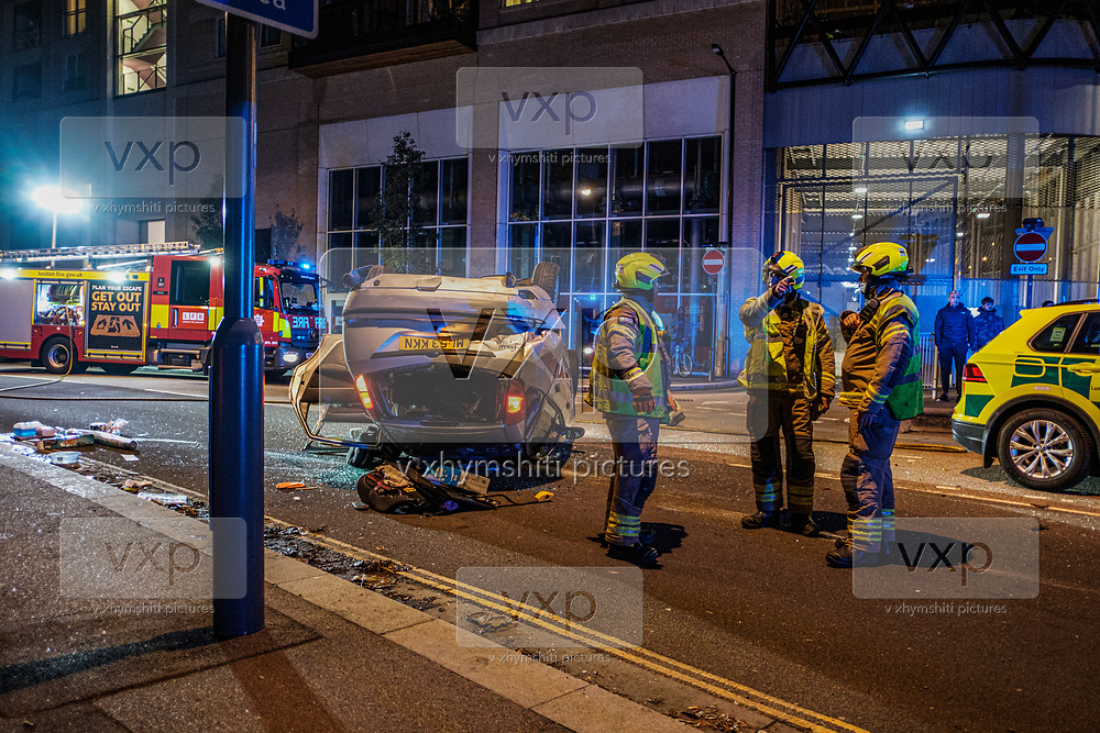 """Fire Brigade members at the crash site after Two Cars crashed at Newham Way (A13) off towards Rathbone Street. A ford Escort flipped over a parked up Mercedes in Canning Town, East London on Saturday, Oct 17, 2020. """"This is a notorious spot for incidents in this area,"""" residents said. All people involved in the incident including children came out okay with a few needing stretchers. """"I saw an Asian lady at her early thirties that was screaming and she was saying that there were two children in the car,"""" a witness told VXP Photographer at the scene. The witness told VXP that the other person who is believed to be the father was also stuck inside. (VXP Photo/ Ehimetalor Unuabona)"""