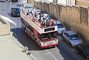 Tourists double decker open top sightseeing bus in Valletta, Malta