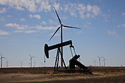 An oil well in the west Texas desert near wind turbines generating electrical power at Horse Hollow Wind Farm, Nolan county, Texas the world's largest wind power project.