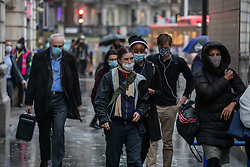 © Licensed to London News Pictures. 03/12/2020. London, UK. Commuters wearing masks brave the cold and rain as they arrive in Westminster, London on the 2nd day of the new Tier 2 restrictions for London as weather experts predict a cold weekend ahead with heavy showers and snow. Top scientists have warned that face coverings and restrictions could be necessary for months to come dispute the rolling out of the new Pfizer/BioNTech's coronavirus vaccine which is expected to arrive in the UK today. And more woes for hight street workers as 20,000 jobs are at risks after the collapse of Topshop and Debenhams this week. Photo credit: Alex Lentati/LNP