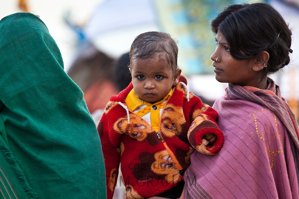 Indian mother with child at Dashashwamedh Ghat in Holy City of Varanasi, Benares, India