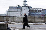 To the world, Chernobyl is a place of danger, but for locals, Chernobyl is simply a way of life.<br /> <br /> On April 26, 1986, an explosion at the Chernobyl Nuclear Power Plant changed history, sending radiation and political shockwaves across Europe.  After the accident, nearby towns and villages were first evacuated, and then abandoned.  A generation later, the Chernobyl Exclusion Zone has become terra incognita for mostóinaccessible, misunderstood, and terrifying.<br /> <br /> Inside the Exclusion Zone, however, life goes on.  More than 3,000 workers manage the Zone, living in Chernobyl town during 4 and 15-day shifts.  Another 3,800 employees commute daily to work at the Chernobyl plant.  Some 400 elderly villagers have illegally resettled their homes and farms inside the Zone.<br /> <br /> Outside the Exclusion Zone are over two thousand villages where radiation fell but people continue to live.  The accident and subsequent evacuations affected residents economically, socially, psychologically óand physically.  <br /> <br /> How much radiation is safe? No one knows.  Thorough medical research has never been done to determine the health effects of long-term radiation exposure.  In the absence of facts, people believe rumors, propaganda, and their own first-hand experiences.<br /> <br /> Why do they stay? A lack of alternatives.  A sense of duty.  Deep ties to the land.  Decent jobs.  Because this is home.<br /> <br /> The closer you are to Chernobyl, the less dangerous it seems.  Instead of radiation, Chernobylites today have new fears.  They worry about their future.  Keeping their jobs.  Opportunities for their children.  Maintaining their hometowns.<br /> <br /> If you lived here, would you stay? <br /> <br /> <br /> Photo Shows: VACHISLAV DANILOV is a medical researcher working at the Chernobyl Nuclear Power Plant (ChNPP or ChAES). He lives in Slavutich, Ukraine, with his son Ilya, one of his eight children, and Ilya's girlfriend Yulia. Here, he walks with other workers to return to the train station at the end of the work day.  Although ChAES stopped ge