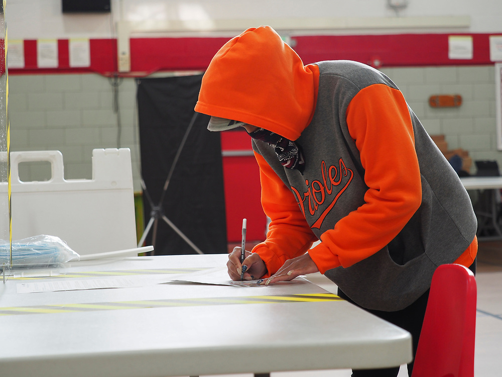 A voter wearing a bandana to guard against the spread of COVID-19 fills out voting paperwork at a voting center in Baltimore during Maryland's 7th Congressional District Special Election.