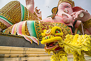 """29 SEPTEMBER 2012 - NAKORN NAYOK, THAILAND:  Thai Chinese style Lion dancers perform in front of a stature of Ganesh during observances of Ganesh Ustav at Wat Utthayan Ganesh, a temple dedicated to Ganesh in Nakorn Nayok, about three hours from Bangkok. Many Thai Buddhists incorporate Hindu elements, including worship of Ganesh into their spiritual life. Ganesha Chaturthi also known as Vinayaka Chaturthi, is the Hindu festival celebrated on the day of the re-birth of Lord Ganesha, the son of Shiva and Parvati. The festival, also known as Ganeshotsav (""""festival of Ganesha"""") is observed in the Hindu calendar month of Bhaadrapada, starting on the the fourth day of the waxing moon. The festival lasts for 10 days, ending on the fourteenth day of the waxing moon. Outside India, it is celebrated widely in Nepal and by Hindus in the United States, Canada, Mauritius, Singapore, Thailand, Cambodia, Burma , Fiji and Trinidad & Tobago.     PHOTO BY JACK KURTZ"""